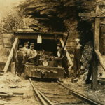 "Entrance to a W. Va. coal mine: a ""drift"" mine. The live-wire was only shoulder -high in places inside, and unprotected. Location: West Virginia. Source: https://commons.wikimedia.org/wiki/File:W._Va._coal_mine_1908.jpg"